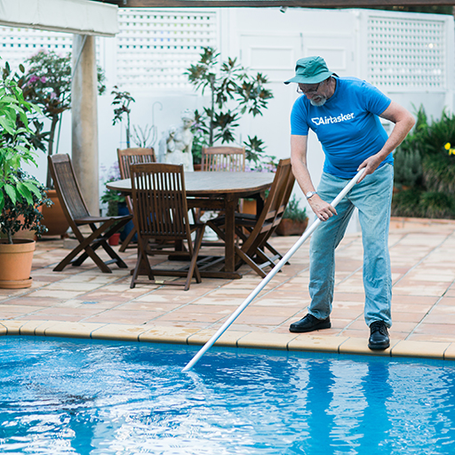Pool cleaner holding a pool net and scooping leaves as he cleans the pool