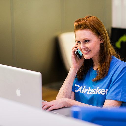 Receptionist answering the phone in an office environment with comopuer in front of her