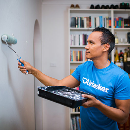 Airtasker standing on a red ladder painting a white door with a paint brush in his hand