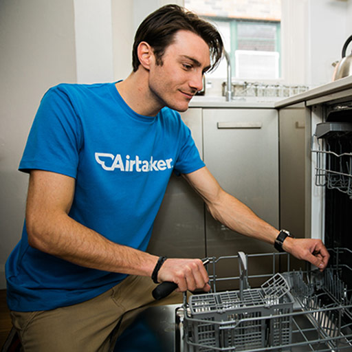 Guy kneeing in front of open dishwasher clearing it out in order to then fix it